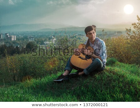 Zdjęcia stock: Młody · człowiek · gry · gitara · znajomych · dziedzinie · muzyki