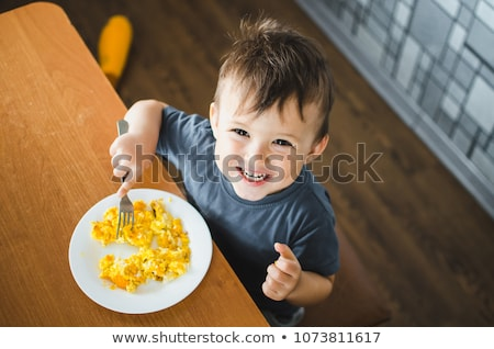 Stock photo: Boy eating sausage and fried egg for breakfast.