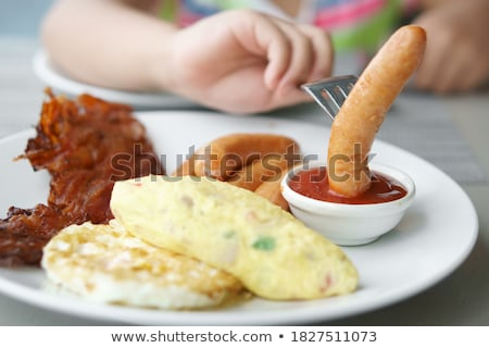 girl eating sausage and fried egg for breakfast stock photo © rastudio