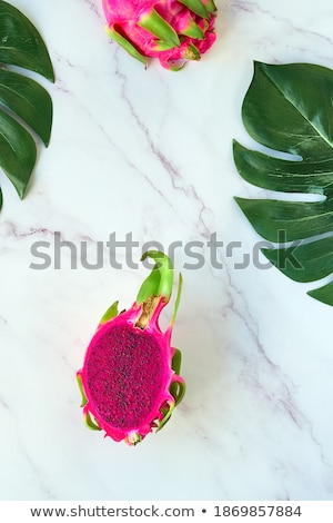 View from above to tropical fruit - pitahaya with green leaf on a pink background, copy space. Top v Stock photo © artjazz