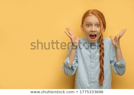 Girl with red hair on a yellow background. The girl is laughing. Stock photo © Traimak