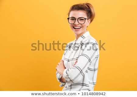 Woman in plaid isolated over yellow wall background. Stock photo © deandrobot