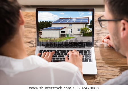 Stock photo: Couple Searching For House With Solar Panel On Laptop