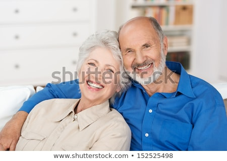 affectionate attractive elderly couple sitting together on a couch stock photo © lopolo