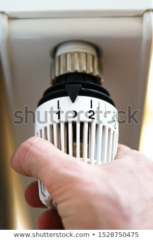 Person Adjusting Temperature On Radiator Stock photo © AndreyPopov
