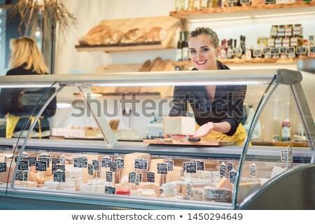 Fiatal eladó hölgy sajt pult áruház Stock fotó © Kzenon
