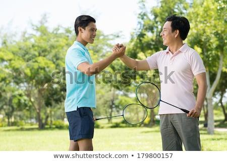 smiling young man with badminton rackets Stock photo © dolgachov