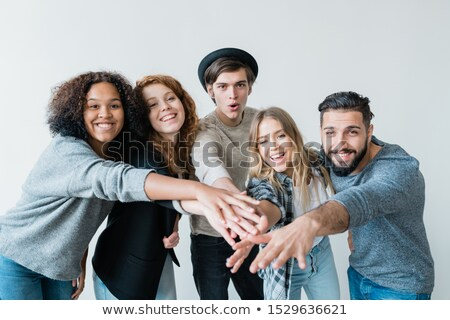 Young playful intercultural friends in casualwear looking at you with smiles Stock photo © pressmaster