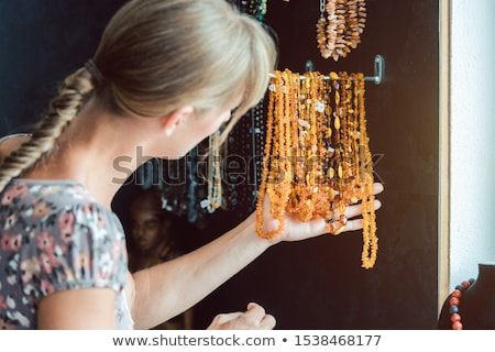 Woman looking at a necklace made of amber Stock photo © Kzenon