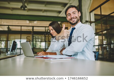 Confident economist showing online information to colleague at meeting Stock photo © pressmaster