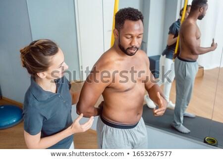 Jonge man fysiotherapie schouder jonge zwarte man vrouwen Stockfoto © Kzenon