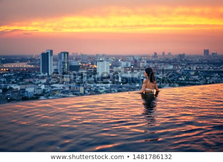 Young woman relax on the edge of the roof top swimming pool Stock photo © GVS