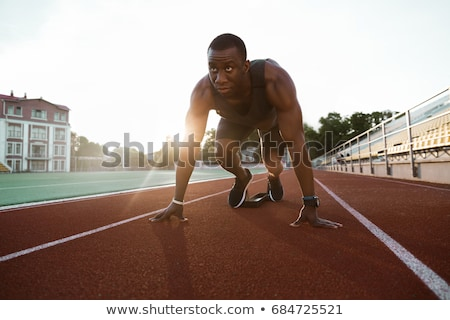 Confident young fit sportsman running on the race track Stock photo © deandrobot