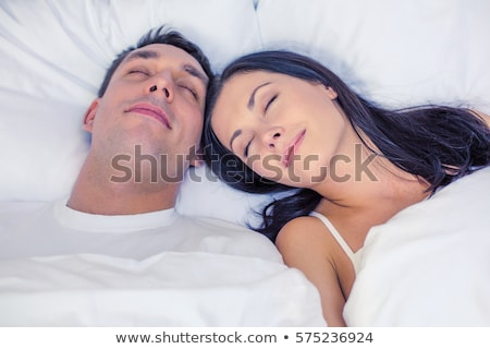 Smiling young man laying on a pillow in bed Stock photo © deandrobot
