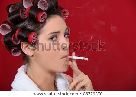 Smoking woman with her hair in rollers Stock photo © photography33