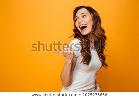 Happy young woman pointing copyspace Stock photo © stockyimages