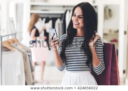 Atrakcyjna kobieta patrząc telefonu komórkowego stałego biały szczęśliwy Zdjęcia stock © wavebreak_media