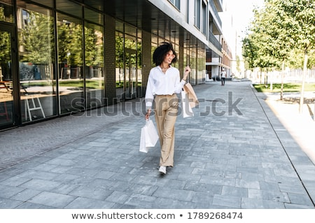 Beautiful shopper with hands full of shopping bags Stock photo © AndreyPopov