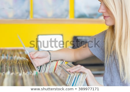 Beautiful young woman selecting a tune Stock photo © dash