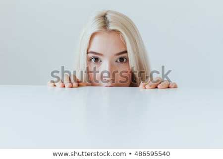 Stock photo: Woman peeping over blank board