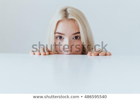 woman peeping over blank board stock photo © deandrobot
