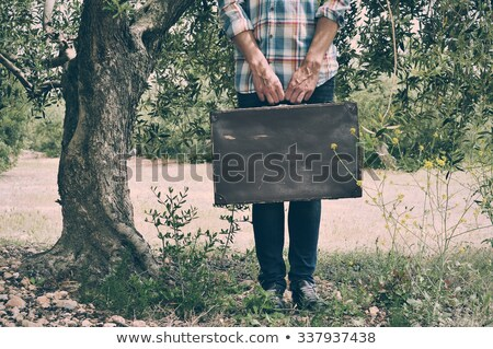 young man with an old brown suitcase in a natural scenery Stock photo © nito