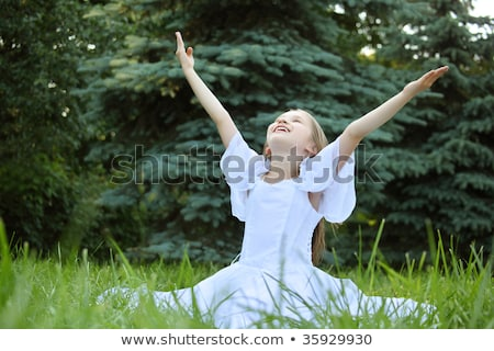 girl in white dress sits on lawn with lifted hands Stock photo © Paha_L