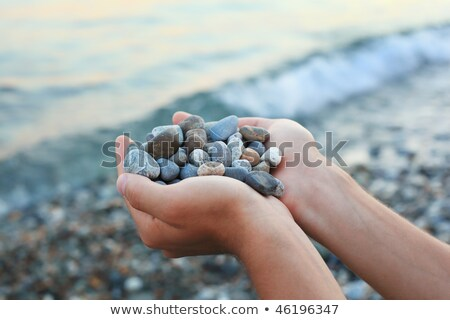 handful of stones in hands against stones and sea stock photo © paha_l