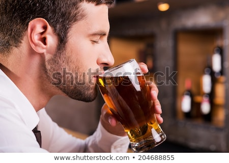 Side view of a young man drinking glass of beer Stock photo © deandrobot