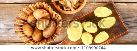 man hands peeling fresh yellow potato with kitchen peeler Stock photo © Valeriy