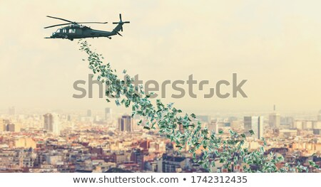 helicopter in sky dropping money over city Stock photo © dolgachov
