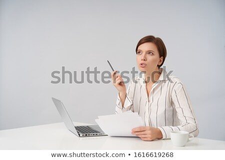 photo of business woman in white shirt looking upward while cove stock photo © deandrobot