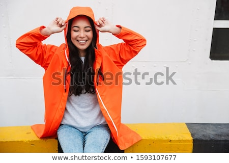 Image of young woman 20s wearing raincoat with hood looking upwa Stock photo © deandrobot