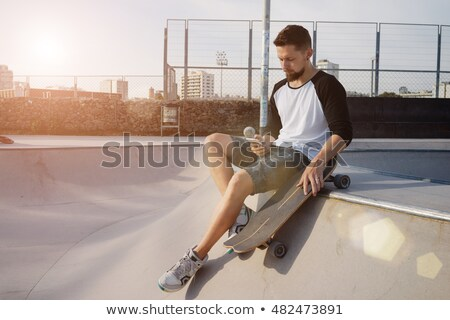Young skater guy sit in the park with skateboard using mobile phone waving. Stock photo © deandrobot