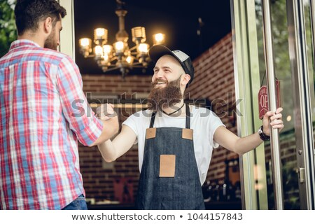 Barber greeting his male customer at the entrance of a cool hair salon Stock photo © Kzenon