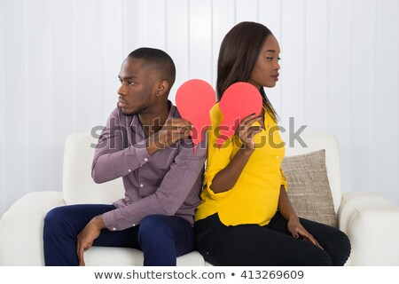 couple sitting on sofa holding broken heart stock photo © andreypopov