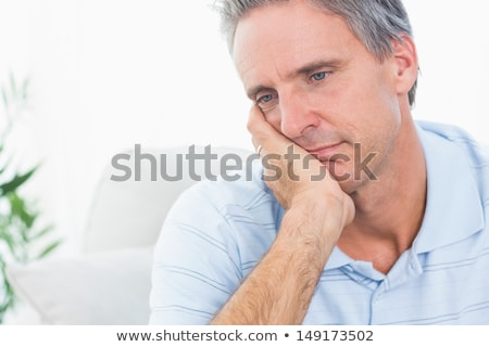 Depressed man thinking on the sofa alone at home Stock photo © Lopolo