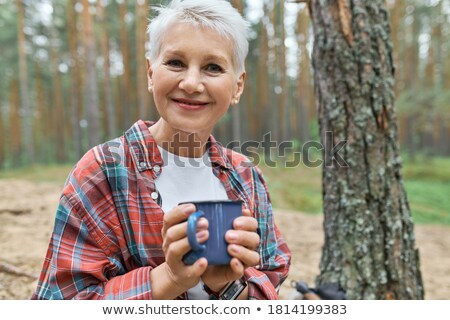 Zdjęcia stock: Mature Backpacker With Tourist Mug Having Hot Drink And Rest