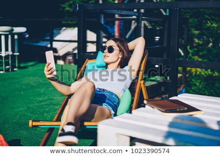Woman taking selfie while lying on sunbed Stock photo © dash