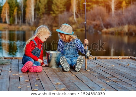 friends with fish, bucket and fishing rod on pier Stock photo © dolgachov