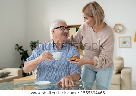 Careful daughter bringing cookies to her happy retired father with cup of tea Stock photo © pressmaster