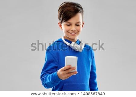 smiling boy in blue hoodie using smartphone Stock photo © dolgachov