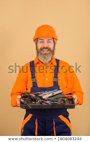 Bearded man builder in helmet holding wrench. Stock photo © deandrobot