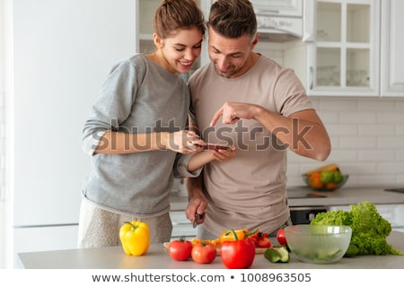 Woman on phone and man preparing meal stock photo © photography33