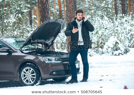 Stock photo: Young man in snow with broken down car