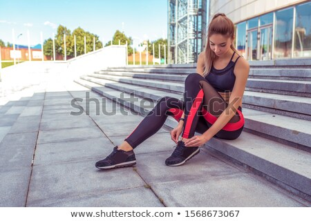 Girl Sitting On Stairs And Tying Shoelaces Stock photo © HighwayStarz
