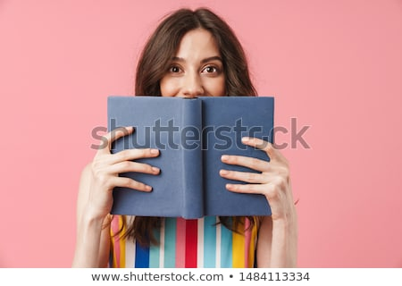 Amazed female teenager reading book Stock photo © deandrobot