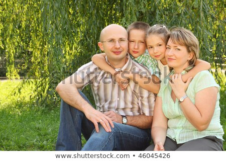 Family with two children sitting at the grass near osier and looking at camera Stock photo © Paha_L