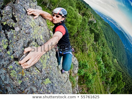 Young white man climbing a steep wall in mountain, rock-climb ex Stock photo © zurijeta