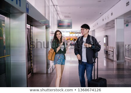 Smiling interracial student couple with backpacks exchanging books Stock photo © deandrobot